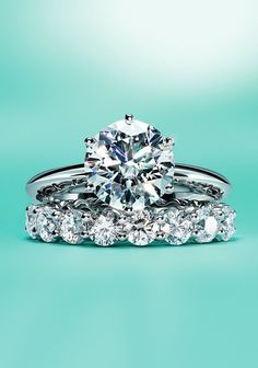 The Tiffany® Setting engagement ring and Tiffany Embrace® wedding band ring in platinum.
