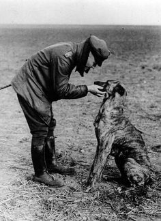 """Manfred von Richthofen, aka """"The Red Baron"""", petting his dog on an airfield during World War I."""