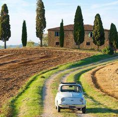Italien wie man es sich vorstellt: Oldtimer Fiat mit typischem Toskana Haus und toskanischer Landschaft im Hintergrund.