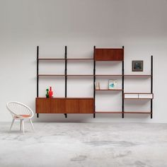 """Poul Cadovius Royal System floating wall unit with dressoir / cabinet Danish modern teak floating wall unit Designed by Poul Cadovius for ROYAL SYSTEM. Multiple shelves (9) and 3 compartments, 1 with wood gliding doors and shelve inside. 1 foating dressoir / cabinet. The Wall unit is signed """"ROYAL SYSTEM Design Poul Cadovius""""."""