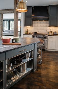 Stunning tri-tone kitchen with off-white lower cabinets paired with brass hardware and soapstone countertops below a subway tiled backsplash which highlights a stainless steel range with black range hood and brass rail framed by dark gray upper cabinets.