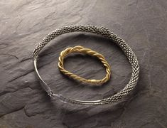10thC-11thC, Viking. Silver neckring of twisted wires; ends beaten into two long expanding terminals ornamented on upper surface with rows of stamped triangles and ending in hook.