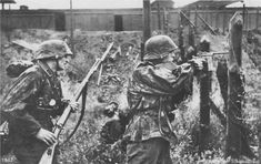 A Waffen SS soldat firing a Mauser M712 Schnellfeuer, the fully automatic version of the Mauser C96. The rearward man holds a standard issue Kar 98k.