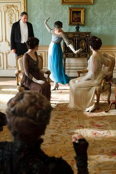 In the drawing room of Downton Abbey, youngest daughter Lady Sybil shows off her evening gown by taking a turn on a gold and red Aubusson rug. The addictive PBS drama has sparked a revival of Edwardian fashions and a heightened interest in classical interiors with Aubusson rugs.  Image courtesy of enchantedserenityperiodfilms blog.