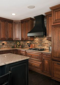 kitchen backspash stone tile backsplash ideas wood cabinets under-cabinet lighting black hood