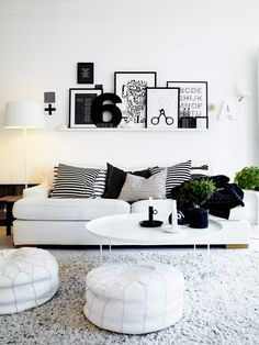 Monochromatic living room with shelves displaying a collection of art, and a white sofa