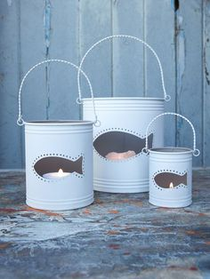 Lovely metal hurricane lanterns with a fish cut-out & a contemporary chalky white finish outside and a natural taupe inside. Tin Can Lanterns, Hurricane Lanterns, Candle Lanterns, Coastal Style, Coastal Decor, Diy Luminaire, Pot A Crayon, Tin Can Crafts, Cottages By The Sea