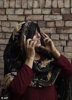 Years of abuse: Pakistani Allah Rakhi, 51, whose husband sliced off her nose and slashed her right foot with a razor in 1980, when she was 19. After marrying at 13, Rakhi suffered six years of abuse at the hands of her husband, right, she holds a photo of them before the attack