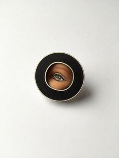 "This sweet Eye Pin features a salvaged brown Barbie doll eye encased in hand-fabricated sterling silver setting with a black resin surround. A lovely accessory to spark up a conversation! Pin comes with a versatile nickel silver tie tack pin back and looks wonderful on coats, blazers, sweaters, hats, ties, scarves, handbags, etc! Measures approx. 1"" in diameter. Oxidized silver finishing with artist signature on the back. Entirely hand-fabricated from start to finish. Why be boring? Wear…"