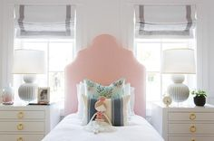 Beautifully appointed pink and white girl's bedroom is fitted with two Bungalow 5 Jacqui 3 Drawer Nightstands lit by Bungalow 5 Meridian Double Gourd Lamps placed in front of windows covered in Pottery Barn Grosgrain Ribbon Cordless Roman Shades flanking a Serena & Lily Pondicherry Bed placed on a gray rug and dressed in white bedding topped with floral and blue striped accented pillows.