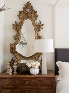 Modern-leaning, streamlined table lamps flanking the four-poster bed perfectly balance an ornate antique mirror. While the lamps match, Tara used mismatched bedside tables and wall decor on either side.
