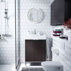 A small white bathroom with LILLÅNGEN washbasin and wall cabinets in black brown.