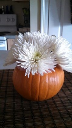 This is a fun idea for using pumpkins this fall! Hollow out a pumpkin, place a jar, vase, or other container inside with water, place in few stems of flowers (in this case, spider mums), and you have a great DIY centerpiece! Shop spider mums and other beautiful fall flowers at GrowerBox.com.