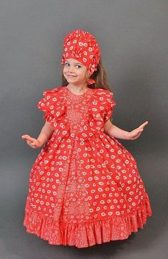 A smiling girl is wearing a dress in the Russian style.