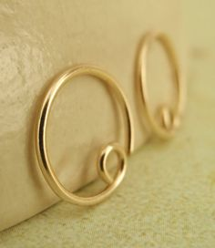 These stylish handcrafted 20 gauge Solid 14kt Gold Hoops will fit and feel wonderfulI make this from 14kt Solid Yellow Gold wire which is Made in the USA. Each listing is for a pair.  They measures 10mm; the ends are de-burred so they will be smooth and wont ouch when you put them in. How do you put them in? Just give a little twist, insert and then twist to close!  These beautiful hoops can be part of our Switch Earring System. Learn more about it here: https://www.etsy.com/l...