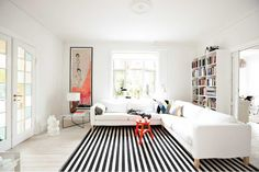 white living room black and white striped rug bookshelves behind sectional red accents