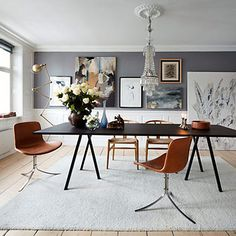Charcoal grey wall looks great against the bold dining furniture and pale backdrop