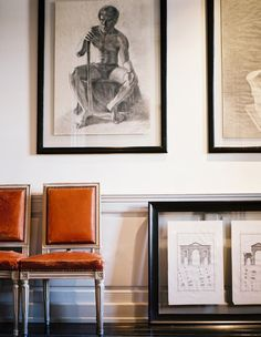 Furniture Photo - A pair of leather chairs beside a grouping of framed art