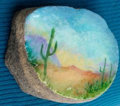 titled: Desert Rock A slice of rock I found had this almost flat top [and bottom], just right for painting on; Sealed with a high gloss clear over my acrylics. measures 3 1/2 across