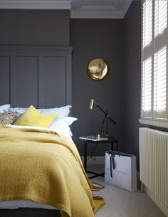 Flashes of textured yellow and pools of gold bring life and style into this chic bedroom, proving dark walls don't mean a dark atmosphere.