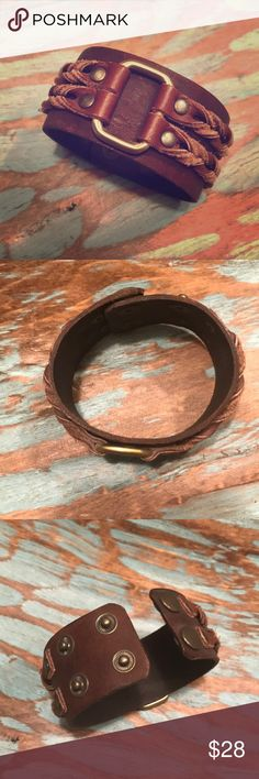 """•Unisex Leather Cuff w/ Braided Design💚SALE💚 This beautiful cuff is made of genuine brown leather, with a contrasted braided leather & brass square, makes for a great design. This is perfect for a larger wrist. I purchased this for my husband but he no longer wears it. You'll see 2 snap lengths for an 8"""" or 9"""" wrist. Has a vintage feel, no real signs of wear, but any signs you see just add to the feel of the cuff! EUC. I believe the snaps/rivets/metal is probably brass? It's not silver or…"""