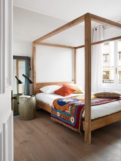 Whitewashed brick complements a minimal wooden bed frame in this