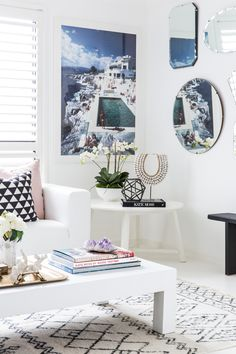 Gorgeous light and bright living room in mostly whites with Slim Aaron artwork. Great coffee table styling and a mirror gallery wall - Simone Duckworth's home featuring Hotel Du Cap Eden Roc available from Kristy Lee Interiors, styled by Claudia Stephenson, photographed by Hannah Blackmore featured in Adore Home Magazine
