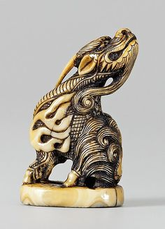 A good possibly marine ivory seal netsuke of a suisai. Late 18th century  Seated on its haunches, the head turned back, with a long slender horn and a long beard, the body covered by finely engraved scales and a small carapace on the back. Beneath the oval base a seal character in relief.