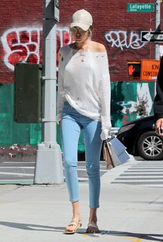 Gigi Hadid in blue skinny jeans with a white sweater and a leather cap.
