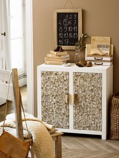 Wooden furniture painted white whose doors are covered with bark tile and handles are birch branches.