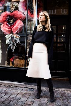 Pernille Teisbaek for Vestiaire Collective wearing a black sweater and a rose skirt.