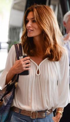 Who made Cindy Crawford's brown print bag and white long sleeve top?