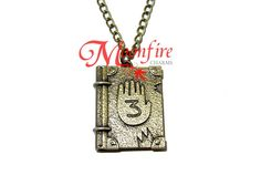 This pendant features Journal from Gravity Falls.The bronze-plated pendant measures 3 cm by cm. Gravity Falls Journal 1, Gravity Falls Cosplay, Grabity Falls, Dipper And Mabel, Fall Over, Journal 3, Over The Garden Wall, Things To Buy, Stuff To Buy