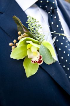 Green orchid boutonniere + navy blue polka dot tie but with grey suit
