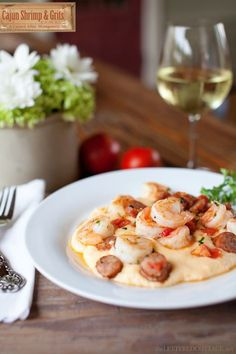 Cajun Shrimp & Grits by A Catered Affair 1 cup grits 3 cups water 1 TBS salt 1/2 cup butter 1-1/2 cups cheese: cheddar, smoked gouda, pepper jack, parmesan 1 cup heavy cream 1 tsp white pepper 1-1/2 lbs fresh jumbo shrimp 1 cup sliced smoked sausage 2 TBS chopped fresh parsley 1 cup diced tomatoes & chilies, drained (I used Rotel tomatoes) 2 cloves garlic, minced 1 TBS cajun seasoning Olive oil