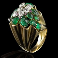 Striking cluster ring designed as a fluted yellow gold mount set with carved, leaf design emeralds punctuated with cabochon rubies within individual collets and a central cluster of brilliant-cut diamonds Yaeche, Paris circa 1945.