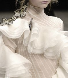 Alexander McQueen 2006. The excessive use of frills executed with white organza silk generates a sense of lightness and innocence in the garment. The use of white and beige generates a sense of naivety and daintiness that can sometimes be likened to the characteristics of an ideal woman during the Victorian times.
