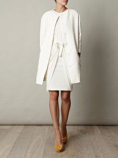 Sharpen up your new-season ensembles with this white Broderie Anglaise coat by Giambattista Valli. Pair this texture-rich piece with colour-pop heels for a modern take on minimalist dressing. Styled here with YSL pumps and Giambattista Valli dress.