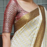 elegant cream and gold saree, with a broad dull gold sequined bands. A kerala saree with a twist.