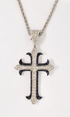 "Cross of diamonds and sapphires is simply stunning. Beautiful quality gems and unique design features the sapphires set against black rhodium and 18k white gold contrasting with the diamonds. Diamonds .42ct twt, sapphires .61ct twt, cross approximately 1 3/4"" X 1""."