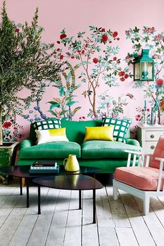 Fun and fresh living room with pink floral wallpaper and a green sofa.