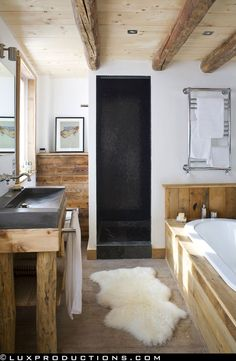 wooden everything bathroom, concrete sink, sheepskin, black doorway