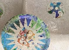 This tile is found on the ceiling of Parc Güell, in the Hypostyle Room.  Although most of the park is decorated in tile, the ceiling is unique in that it offers circular, grandiose designs.