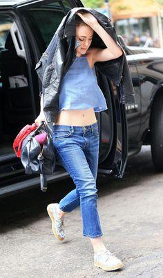 Street style da atriz Dakota Fanning com blusa cropped e calça jeans.