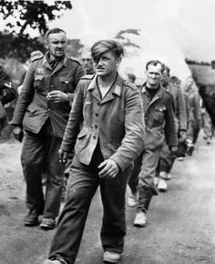 column of German prisoners, captured in fighting for the outer defenses of Cherbourg are marched to a prisoner of war stockade behind the lines on June 29, 1944.