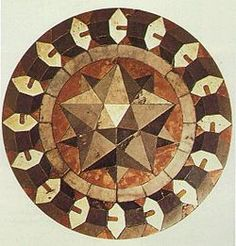 Marble mosaic showing a small stellated dodecahedron and a ring of hexagonal prisms, on the floor of St Mark's Basilica, Venice.
