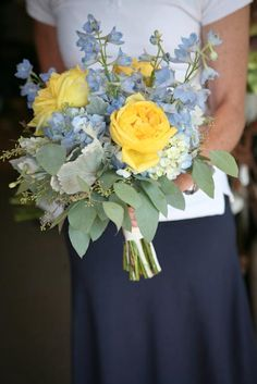 Blue and yellow wedding bouquet. Perfect for the bride or bridesmaid. Designed with blue hydrangea, yellow roses, light blue delphinium, dusty miller, and seeded eucalyptus. Backyard Garden Florist.