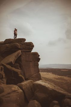 Couple stood on top of a cliff at Stanage Edge, in the Sheffield & Derbyshire Peak District.