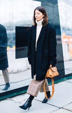 navy blue black coat white turtleneck sweater brown plaid pants black boots