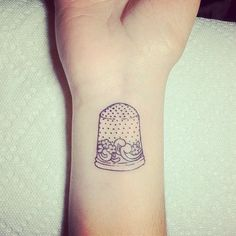 Thimble tattoo on the wrist. -I think I might like one on my fingertip in reference to Peter Pan